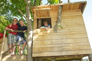 Kinder posieren im Baumhaus