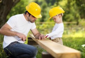 Mann und Kind mit Helmen und Holz