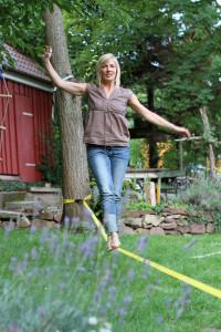 Frau auf Slackline im Garten