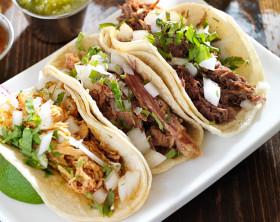 Drei Tacos, gefüllt mit Hähnchen, Zwiebeln und Kräutern