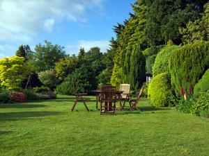 Sitzecke umringt von Hecken und Bäumen als natürliche Begrenzung