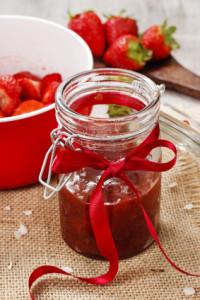 Erdbeerkompott in einem Einmachglas mit roter Schleife