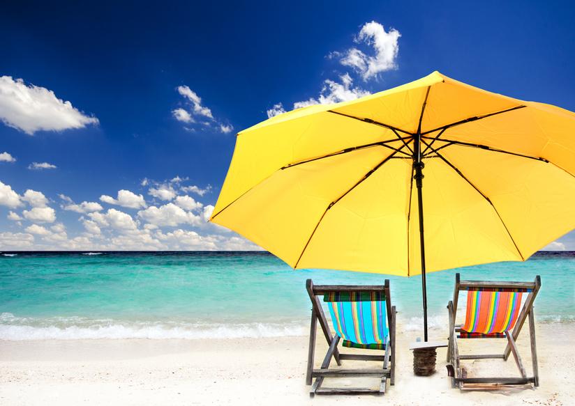 Strandidyll: zwei Liegen unter einem gelbem Sonnenschirm
