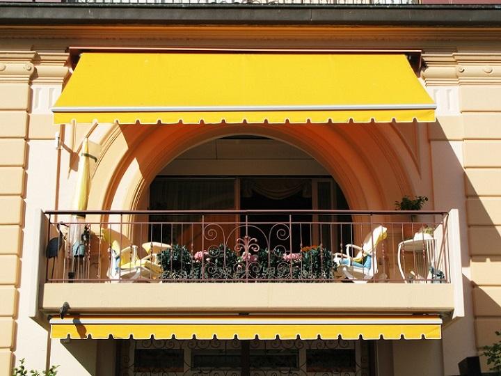 Gelenkarmmarkise mit gelbem Bezug