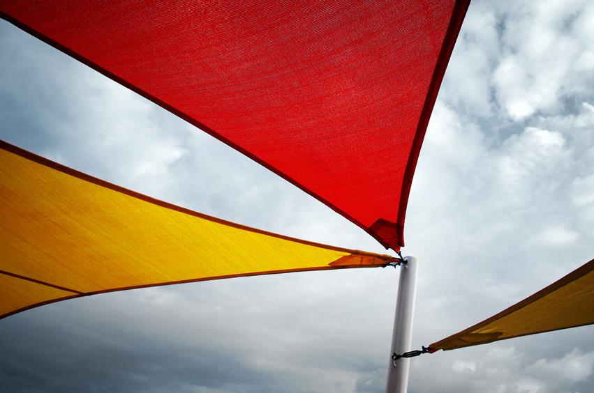 Drei farbige Soonnensegel an einem Mast