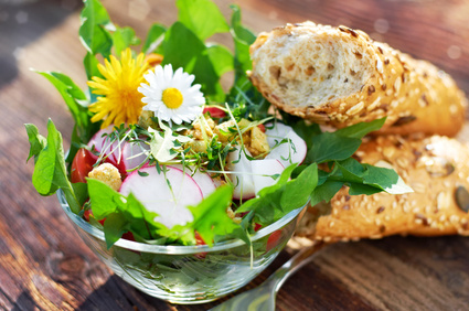 Knackiger Frühlingssalat mit essbaren Blüten und Baguette-Stangen
