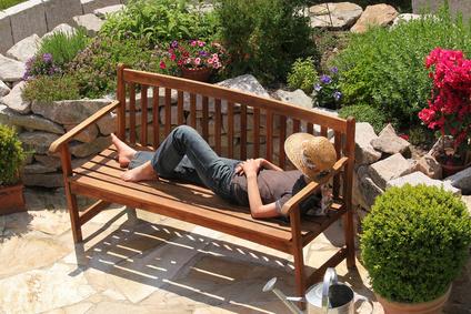 Holzbank mit schlafendem Menschen