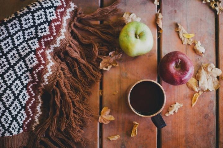 Wolldecke, Äpfel, Becher auf Holztisch